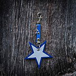 Star. Blue with blue textile K1 clasp fastening and airplane pendant.