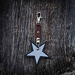 Star. Dark grey with brown textile K1 clasp fastening.