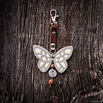 Off white butterfly with K1 fastening, brown leather, rowan beads