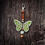 Green butterfly with K1 fastening, brown leather, rowan beads