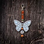 Light blue butterfly with K1 fastening, brown leather, rowan beads