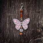 Light pink butterfly with K1 fastening, brown leather, rowan beads