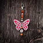 Dark pink butterfly with K1 fastening, brown leather, rowan beads