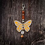 Yellow butterfly with K1 fastening, brown leather, rowan beads