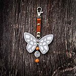 Bright white butterfly with K1 fastening, brown leather, rowan beads
