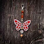 Red butterfly with K1 fastening, brown leather, rowan beads