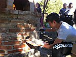 Italian students practice plastering a pizza oven