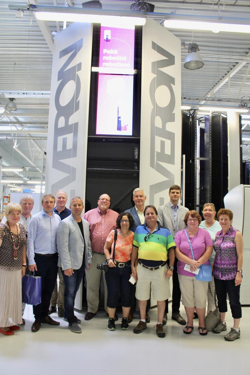 Visitors in Cleveron's factory posing in front of the Cleveron 401 parcel robot